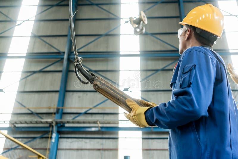 Erfahrene asiatische Arbeitskraft, die industriellen Haken steuert lizenzfreie stockfotografie