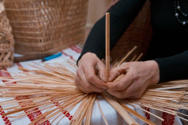 Erfahrene Frau flicht eine Strohtasche an der ethnographischen Vorlagenklasse, traditionelle Handwerkskunst an der ethnographisch stockbild