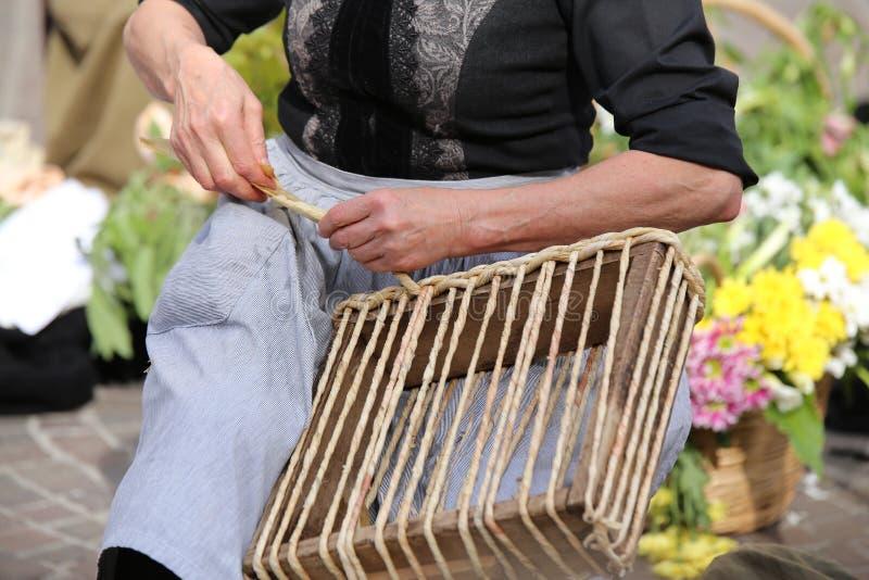 erfahrene Hände einer älteren Frau während Torsion das Stroh einer Tasche stockbild