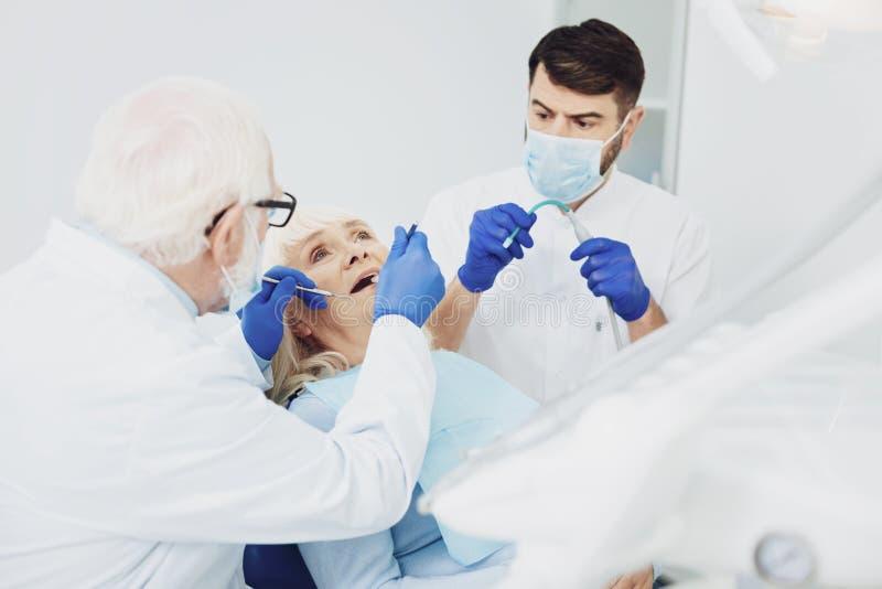 Erfahrene männliche Zahnärzte, die Patienten behandeln stockbild