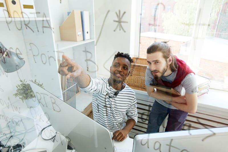 Erfahrene Software Engineers, die Algorithmus kodierend sich besprechen lizenzfreies stockfoto