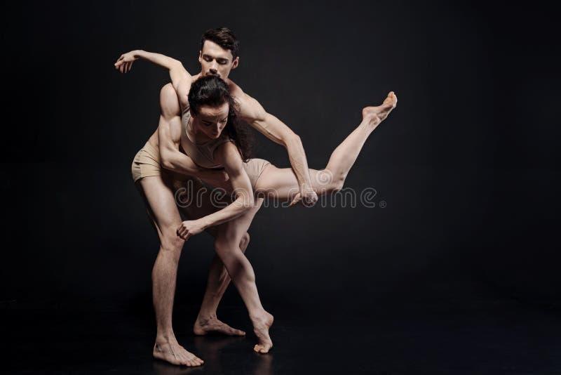 Erfahrene Tänzer, die vor der dunklen Wand durchführen lizenzfreies stockfoto