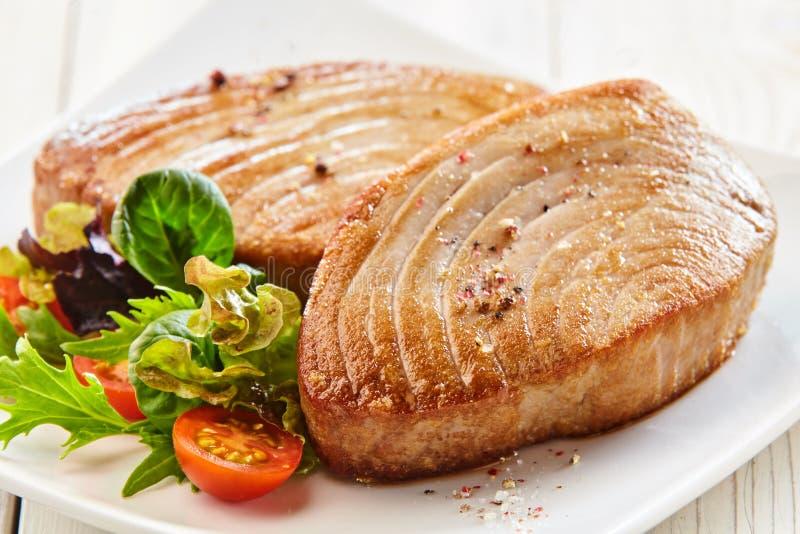 Erfahrene Tuna Steaks auf Platte mit frischem Salat lizenzfreie stockfotos