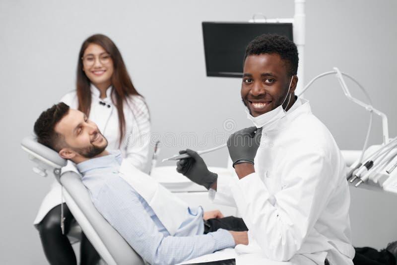 Erfahrener afrikanischer Zahnarzt, der Kamera und das Lächeln betrachtet stockfotografie