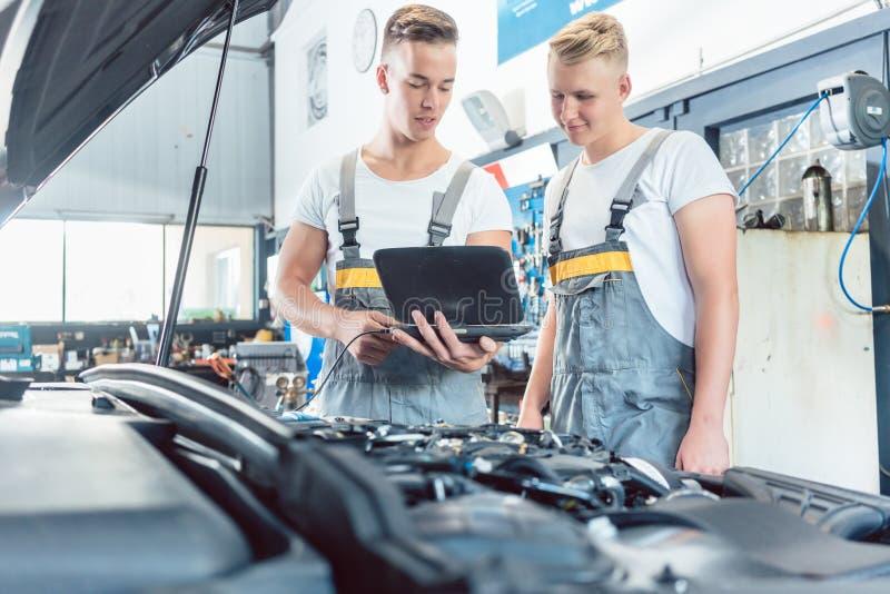 Erfahrener Automechaniker, der einen Laptop für Überprüfungsmaschinenfehlercodes verwendet stockfotografie