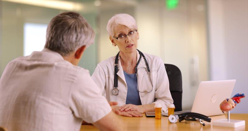 Erfahrener Doktor, der mit älterem Mann im Büro spricht lizenzfreie stockfotos