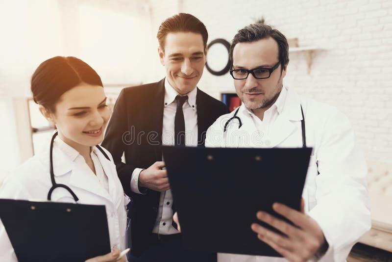 Erfahrener Doktor mit Krankenschwestershowergebnissen analysiert zu lächelndem Geschäftsmann im Büro stockbilder