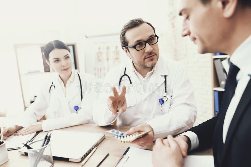 Erfahrener Doktor schreiben zum Patienten über Dosierung von Tabletten im Ärztlichen Dienst vor stockfoto