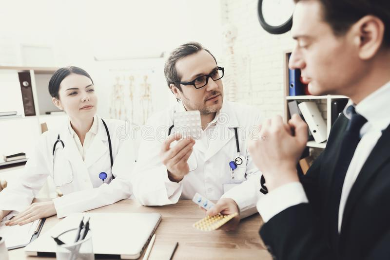 Erfahrener Doktor schreiben zum Patienten über Dosierung von Tabletten im Ärztlichen Dienst vor stockfotos