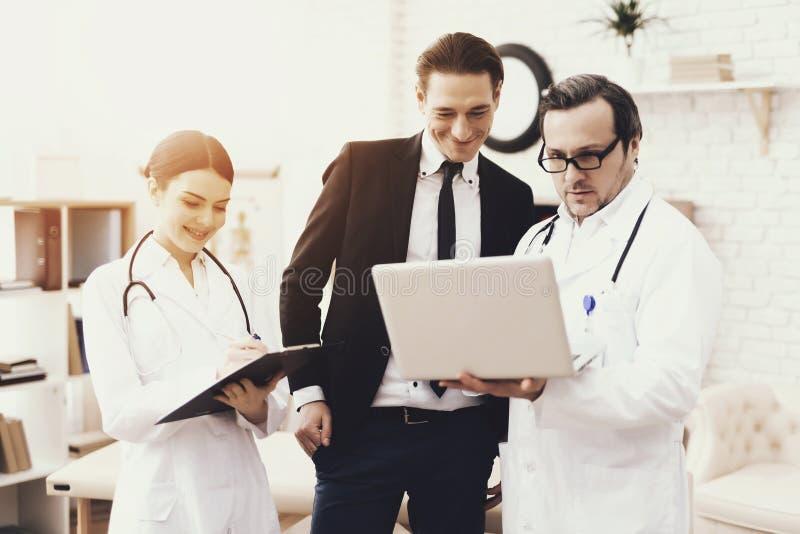 Erfahrener Doktor stellt auf Laptopergebnissen der ärztlichen Untersuchung des erfolgreichen Geschäftsmannes dar lizenzfreies stockbild