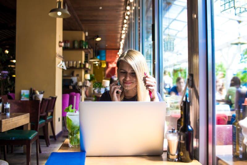 Erfahrener Freiberufler des Oungs-Hippie-Mädchens, der über Mobiltelefon während der Arbeit über modernes Notizbuchgerät nennt lizenzfreie stockfotos