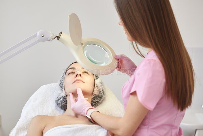 Erfahrener junger Cosmetologist in der rosa Laborkittelholdinglupe in einer Hand, schaltend die Lampe ein und berühren das Gesich stockfoto