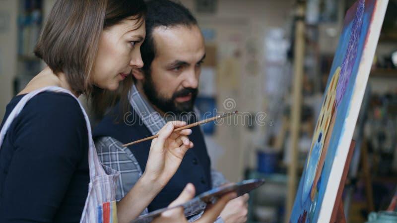 Erfahrener Künstlerlehrer, der Grundlagen der Malerei zum Studenten am Kunstunterricht zeigt und bespricht stockbild