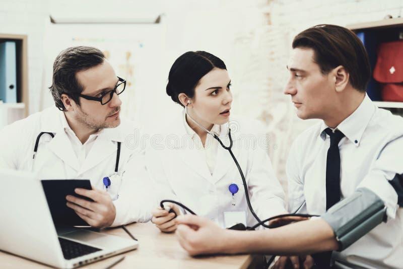 Erfahrener Kardiologe misst Druck des erwachsenen Mannes mit tonometer Hoher Blutdruck stockfotografie