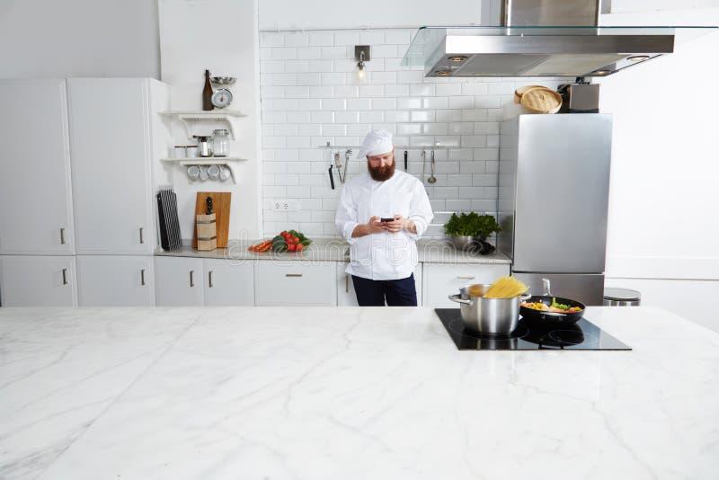 Erfahrener männlicher Chefkoch, der auf großer moderner Küche bei der Anwendung des intelligenten Telefons steht lizenzfreie stockfotos