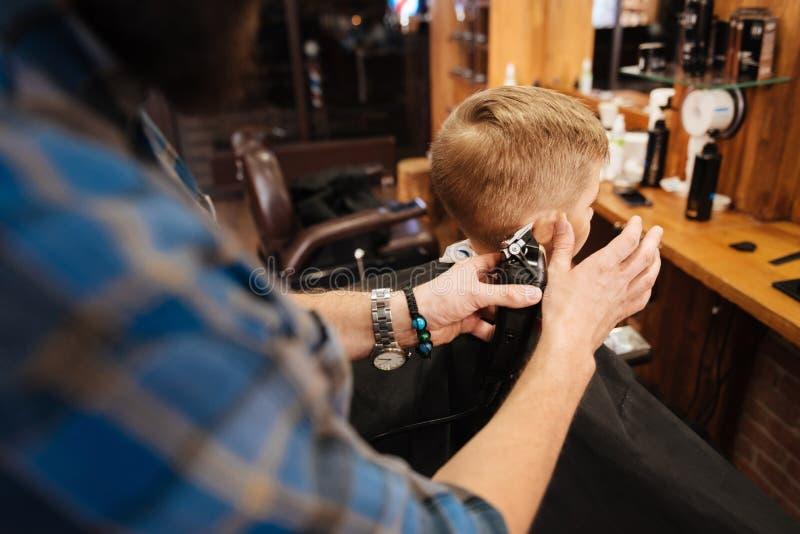 Erfahrener männlicher Friseur, der auf seinem Job fokussiert wird stockbild