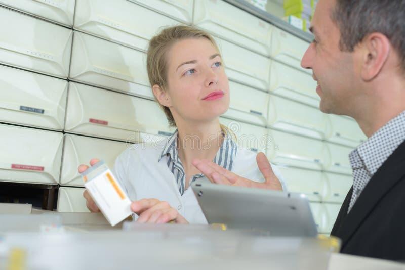Erfahrener Managerapotheker, der weiblichen Mitarbeiter in der modernen Apotheke berät stockfotos