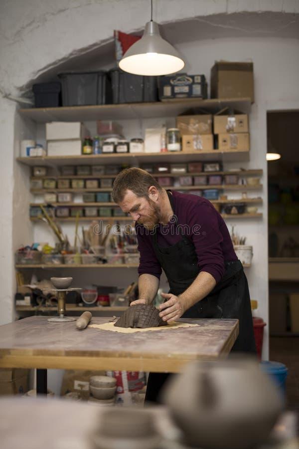 Erfahrener Meister, der Lehmwerkstücke für neues seine Schaffungen vorbereitet lizenzfreies stockbild