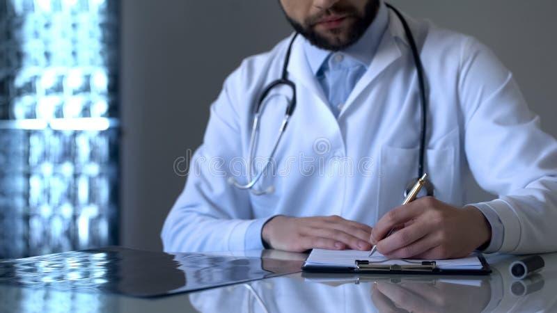 Erfahrener Traumatologist, der Beinröntgenstrahl betrachtet und Anmerkungen in der medizinischen Form macht lizenzfreies stockbild