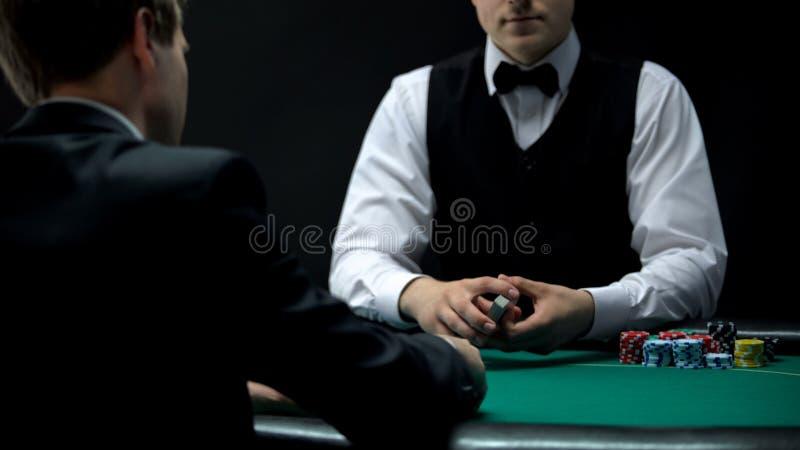 Erfahrenes Croupier, das Kartensatz bereit zu behandeln, Möglichkeit, im Schürhaken zu gewinnen hält stockbild