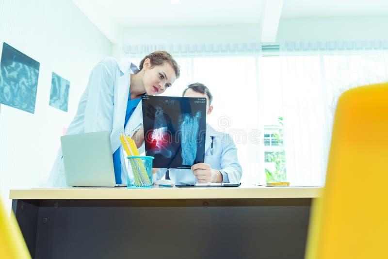 Erfara mannen och kvinnlig doktorsortopedi och lagexperten som diskuterar röntgenstrålefilmen, kirurgi med tolkningen en röntg arkivfoto