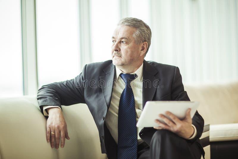 Erfaren affärsman med digitalt minnestavlasammanträde på soffan och att se ut kontorsfönstret arkivbilder