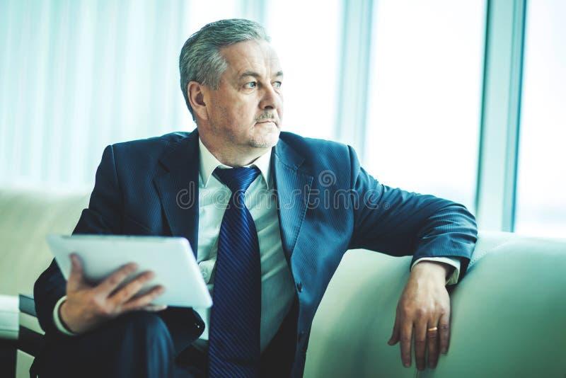 Erfaren affärsman med digitalt minnestavlasammanträde på soffan och att se ut kontorsfönstret arkivbild