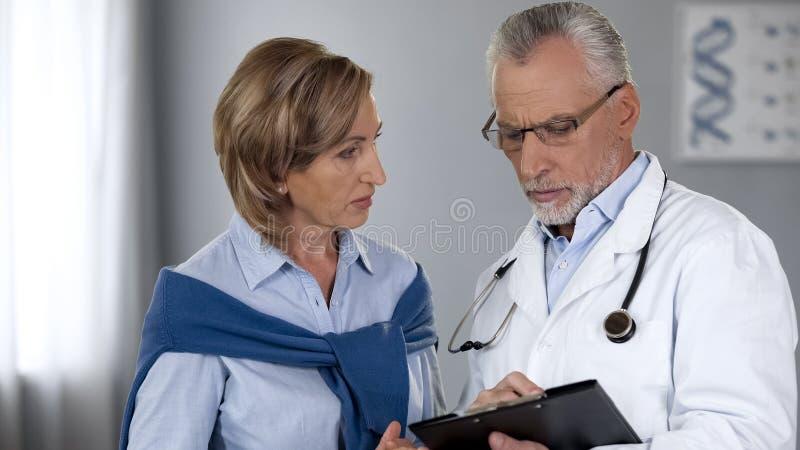 Erfaren doktor som visar resultat till den kvinnliga patienten, sjukdombehandlingsmetod royaltyfria bilder