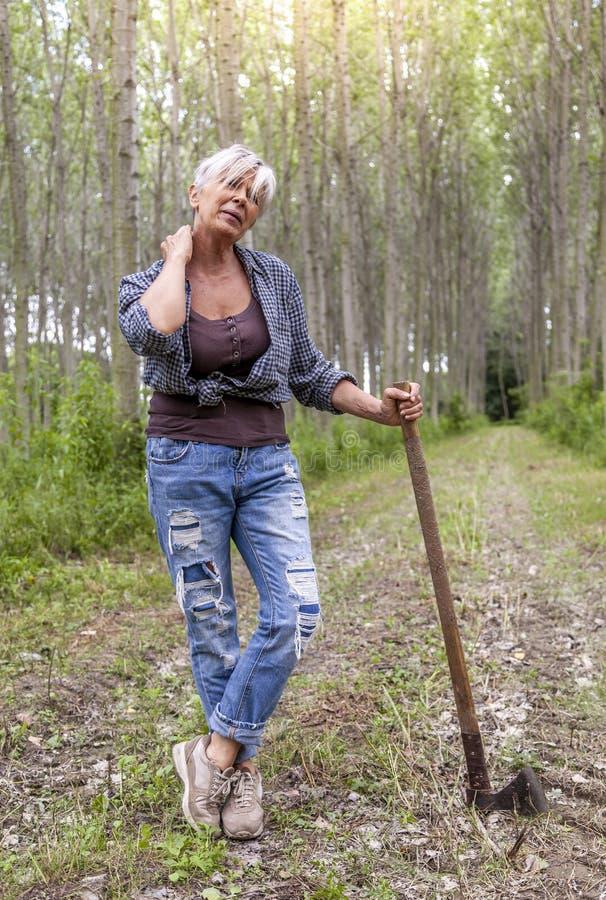 Erfaren kvinnlig skogsarbetare som kopplar av i en skog royaltyfria bilder
