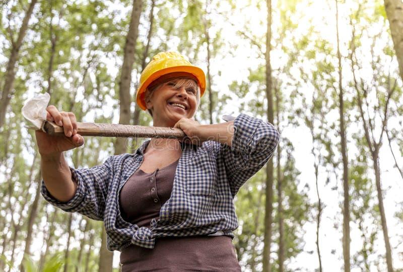 Erfaren kvinnlig skogsarbetare som kopplar av i en skog royaltyfri foto