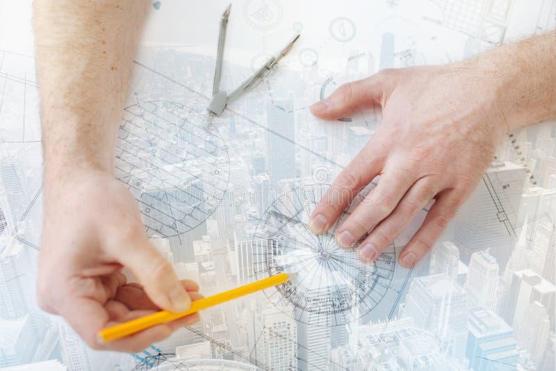 Erfaren tekniker som använder en linjal och en blyertspenna royaltyfri bild