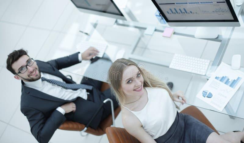 Erfarna företagsanställda som sitter på skrivbordet och ser kameran royaltyfri bild