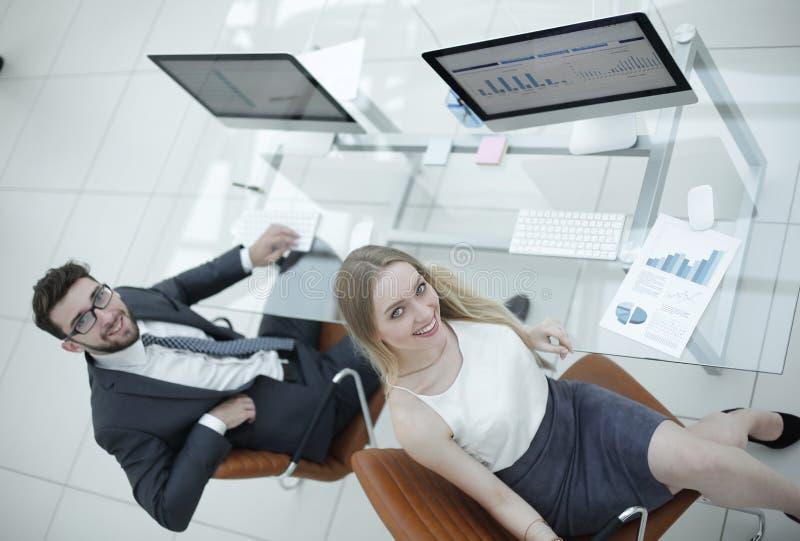 Erfarna företagsanställda som sitter på skrivbordet och ser kameran royaltyfria foton