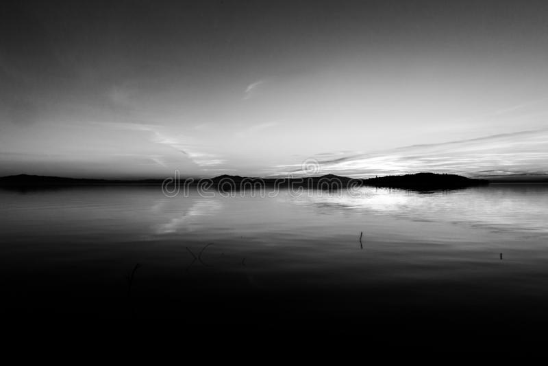 Erfectly symétrique, belle vue de lac Ombrie, Italie Trasimeno au coucher du soleil, avec des formes de nuage sur le ciel photo stock