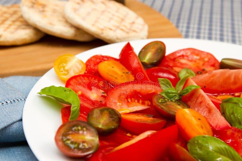 Erfenis tomatoe salade met vlakke broden stock foto