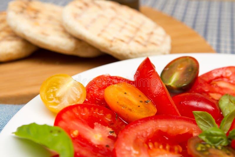 Erfenis tomatoe salade met vlakke broden stock afbeelding