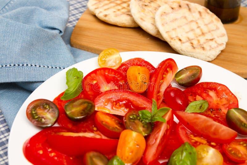Erfenis tomatoe salade met vlakke broden royalty-vrije stock foto