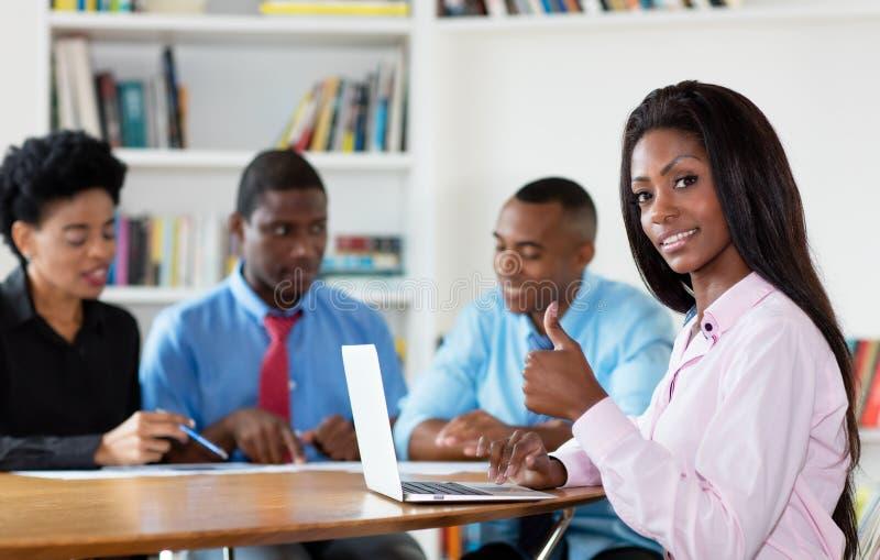 Erfolgreiche Afroamerikanergeschäftsfrau mit Team und Computer stockfotografie