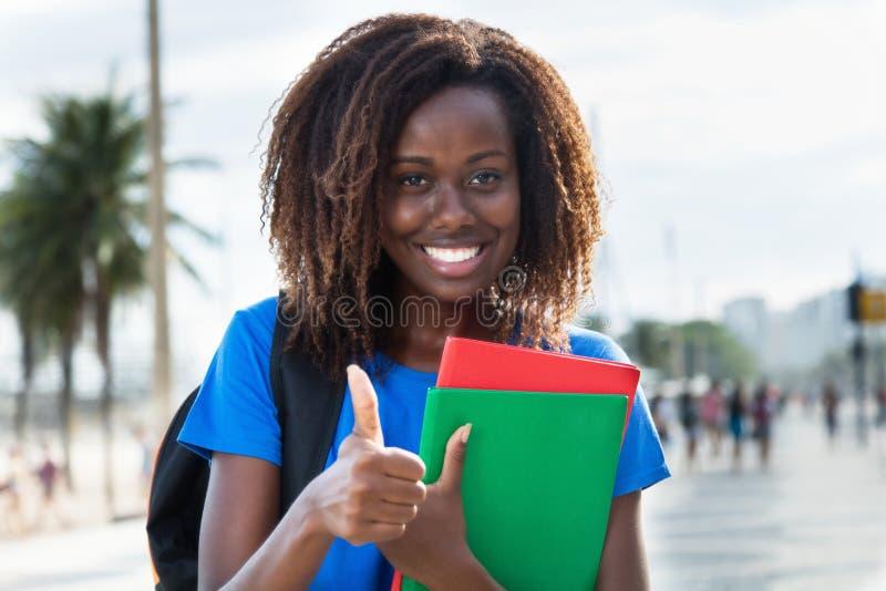 Erfolgreiche Afroamerikanerstudentin, die Daumen zeigt stockfoto