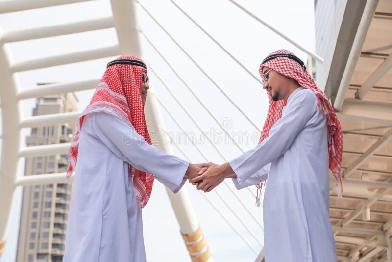 Erfolgreiche arabische Geschäftsleute, die Hände rütteln lizenzfreie stockfotografie