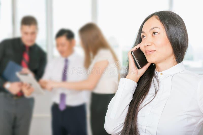 Erfolgreiche asiatische Geschäftsfrau, die Handy verwendet lizenzfreie stockfotografie