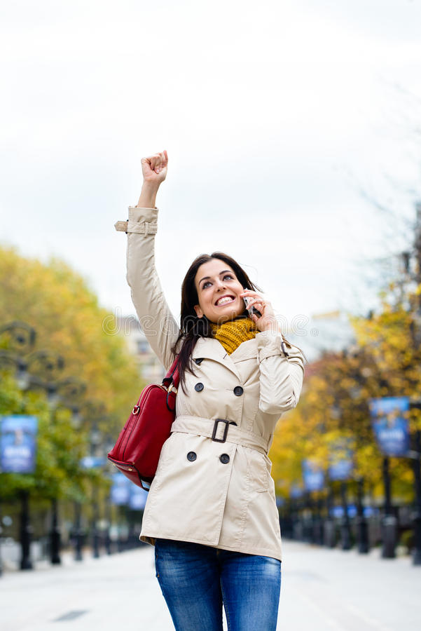 Erfolgreiche Frau beim Mobiltelefonanruf im Herbst lizenzfreie stockfotografie