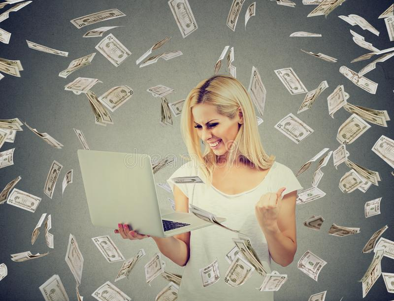 Erfolgreiche Frau, die den Laptop aufbaut das on-line-Geschäft macht die GeldDollarscheine abfallen verwendet stockfoto