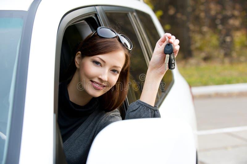 Erfolgreiche Frau mit Tasten vom Auto stockfotografie