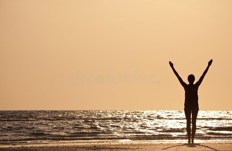 Erfolgreiche Frauen-Arme angehoben am Sonnenuntergang auf Strand stockfotos