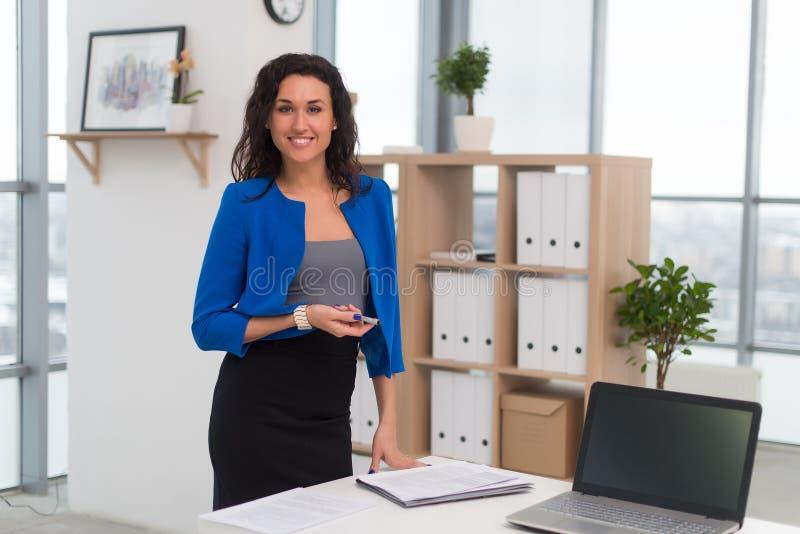 Erfolgreiche Geschäftsfrau, die überzeugt schauen und Lächeln stockbilder