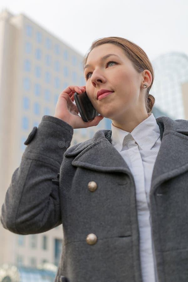 Erfolgreiche Geschäftsfrau, die auf Mobiltelefon beim heraus gehen spricht lizenzfreie stockfotografie