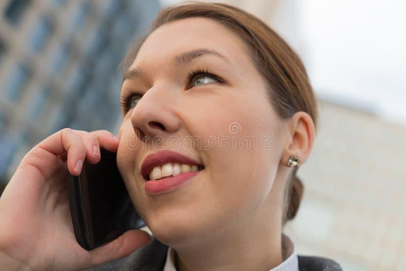 Erfolgreiche Geschäftsfrau, die auf Mobiltelefon beim heraus gehen spricht lizenzfreies stockbild