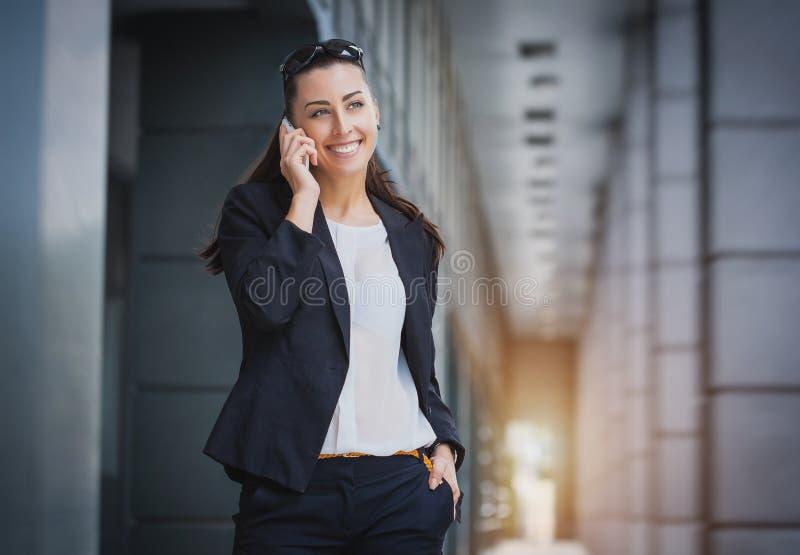 Erfolgreiche Geschäftsfrau, die auf Mobiltelefon spricht lizenzfreie stockfotos