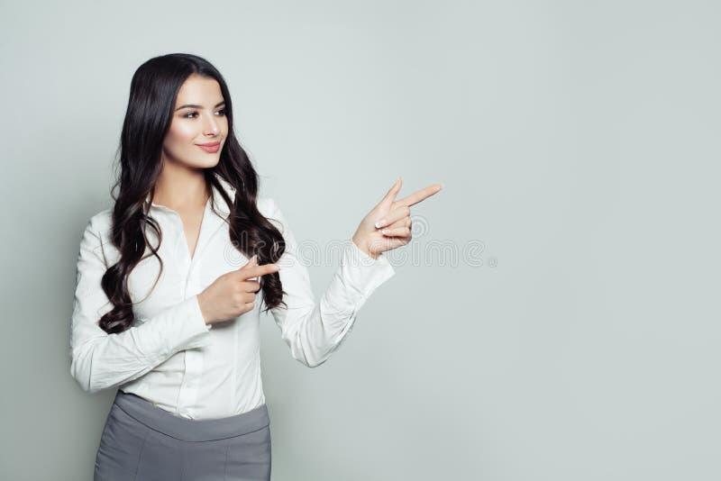 Erfolgreiche Geschäftsfrau, die ihren Finger auf leeren Kopienraum zeigt stockbild